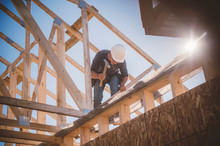 Builder Working On Rooftop Frame Of Building