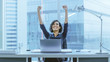 Leinwanddruck Bild - Shot of the Beautiful Businesswoman Sitting at Her Office Desk, Raising Her Arms in a Celebration of a Successful Job Promotion.