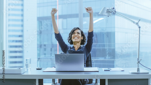 Shot of the Beautiful Businesswoman Sitting at Her Office Desk, Raising Her Arms in a Celebration of a Successful Job Promotion Wallpaper Mural