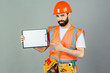 A builder in an orange helmet on a gray background signs something