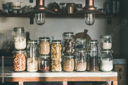 Cadres-photo bureau Graine, aromate Rustic kitchen food storage arrangement. Grains, cereals, nut, dry fruit, flour, pasta kinds in jars over concrete kitchen counter. Clean eating, healthy, vegan, vegetarian, balanced diet concept