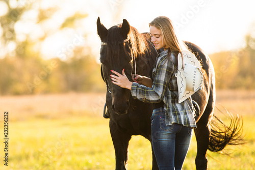 Poster Horseback riding Girl horse rider stands near the horse and hugs the horse. Horse theme