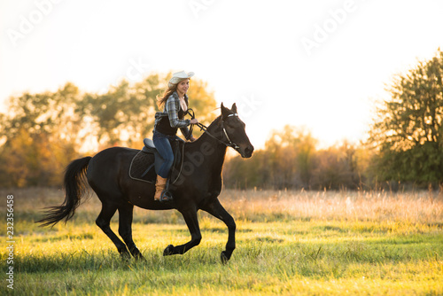 Poster Equitation Girl equestrian rider riding a beautiful horse in the rays of the setting sun. Horse theme