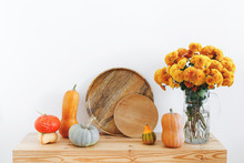 Different Multicolored Decorative Pumpkins, Wooden Plates Or Dishes And Vase With Yellow Chrysanthemums Flowers On A Wooden Table On A Background Of White Wall. Autumn Or Fall Home Interior Decor.