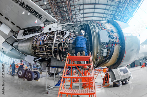 Fotografie, Obraz  Airplane mechanic diagnose repairs jet engine through open hatch.