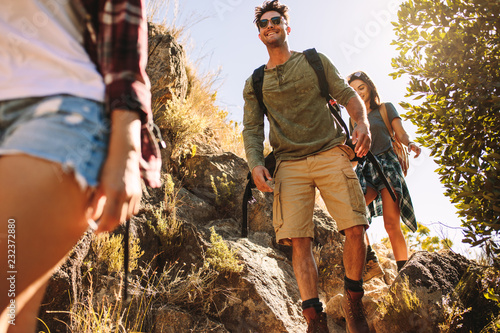 Friends hiking on rocky mountain trail Poster Mural XXL