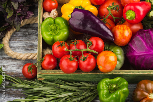 Obraz na plátně  Set of different fresh raw colored vegetables in the wooden tray, light wooden b