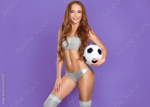 Beautiful girl soccer player with the ball on purple background