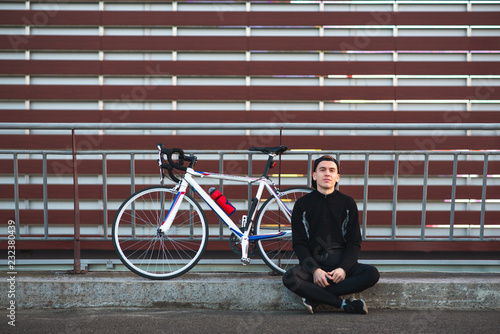Fotografija  Happy cyclist with a bike chip on the background of the wall