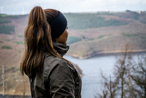 Fotografia Young beautiful female model in hike clothes wearing a headband and pigtail shot separated in front of a nature scenery in the German Eifel region