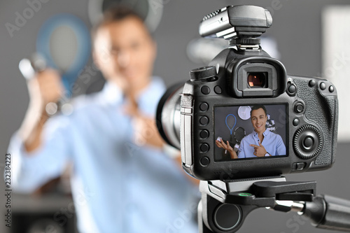 Fotografie, Obraz  Sport blogger recording video indoors, selective focus on camera display