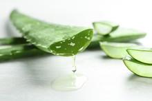 Fresh Sliced Aloe Vera Leaf With Dripping Juice On Light Table, Closeup
