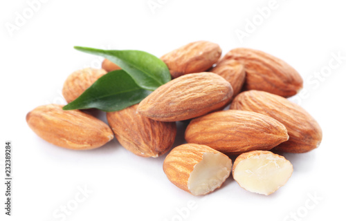 Canvas Print Organic almond nuts and leaves on white background. Healthy snack