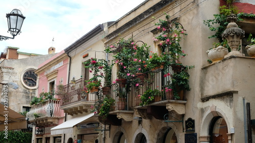 Fototapety, obrazy: Taormina, Province of Messina, Sicily. All around the city there are beatiful balconies, often decorated with flower pots. This is Corso Umberto, the main street of the city.