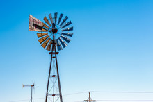 A Traditional Wind Mill Next To A Wind Turbine Create A Juxtaposition Of Old And New.