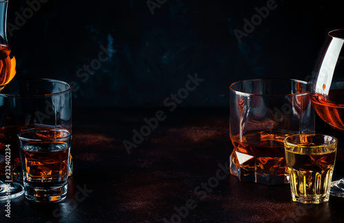 Selection of strong alcoholic drinks in glasses and shot glass in assortent: vodka, rum, cognac, tequila, brandy and whiskey. Dark vintage background, selective focus