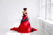 A Young Woman In A Red Dress Is Dancing. Latin Style. Isolate On White