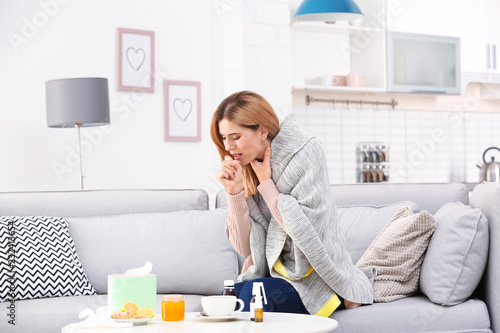 Fotografía Woman suffering from cough and cold on sofa at home