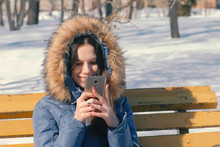 Woman Types A Message On Her Phone Sitting On The Bench In Winter City Park In Sunny Day.