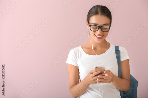Foto  Beautiful young woman listening to music on color background