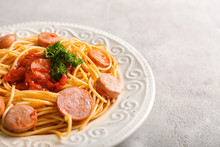 Plate With Delicious Pasta And Sausage On Grey Table