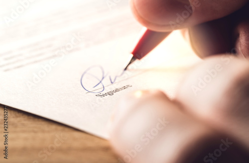 Foto Man writing signature with pen on paper