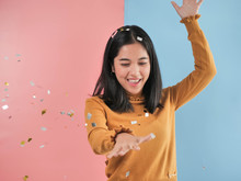 Happy Asian Woman With Falling Silver And Golden Paper Glitter Down.