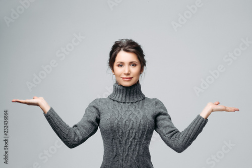 Fototapeta Waist up portrait of smiling woman presenting something, proposing making choice between two things or objects. Attractive brunette looking at camera with happiness. Isolated on gray background obraz