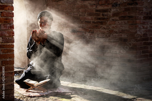 Silhouette of muslim male praying in old mosque with lighting and smoke backgrou Fotobehang