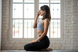 Young sporty woman practicing yoga, doing Alternate Nostril Breathing exercise, nadi shodhana pranayama pose, working out, wearing sportswear, indoor full length, white yoga studio, side view