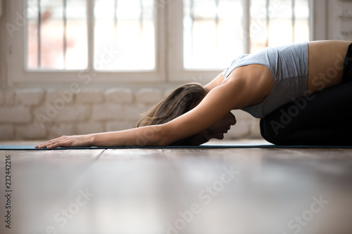 Fotobehang Ontspanning Young sporty attractive woman practicing yoga, doing Child exercise, Balasana pose, working out, wearing sportswear, black pants and top, indoor close, white yoga studio. Well being concept