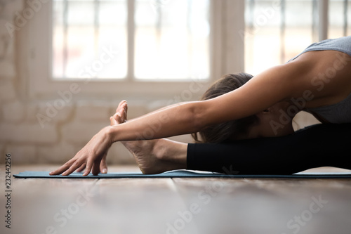Poster Ecole de Yoga Young sporty attractive woman practicing yoga, doing paschimottanasana exercise, Seated forward bend pose, working out, wearing sportswear, black pants and top, indoor close up, white yoga studio