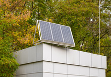 Close-up Of A Building Roof With A Solar Panel On Top, On A Autumn Background.