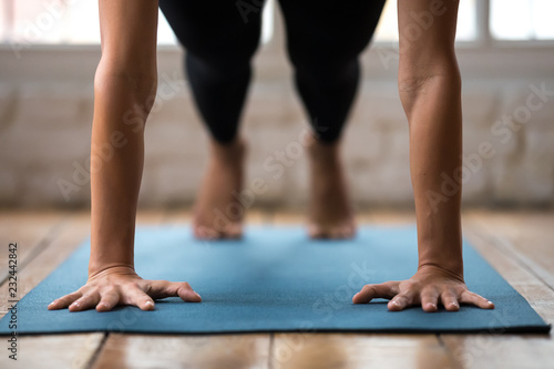 Poster Ecole de Yoga Young sporty woman practicing yoga, doing Push ups or press ups exercise, phalankasana, Plank pose, working out, wearing sportswear, indoor close up, yoga studio. Arms strengthening well being concept