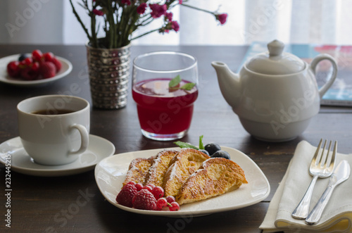 Fotografía  Spanish Torrijas or french toasts with berries and icing sugar for breakfast in hotel restaurant