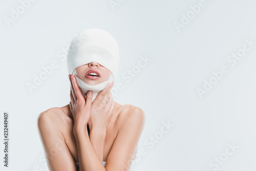 Photo naked woman with bandages on head after plastic surgery isolated on white