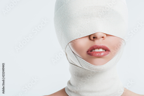 Leinwand Poster close up of woman face with white bandages isolated on white