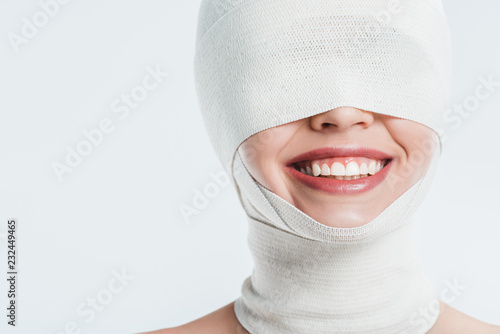 Leinwand Poster close up of woman face with white bandages and smile isolated on white