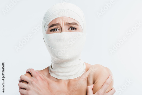 Foto close up of naked painful woman with white bandages over face and head isolated