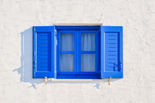 Iconic Blue Greek Style Window On Whitewashed Wall