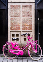 Pink Retro Bike Against Brick House Entrance