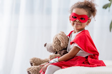 Adorable Little African American Kid In Superhero Costume And Mask With Teddy Bear