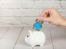 Saving Time Concept. Hand Putting Alarm Clock Into The Piggy Bank
