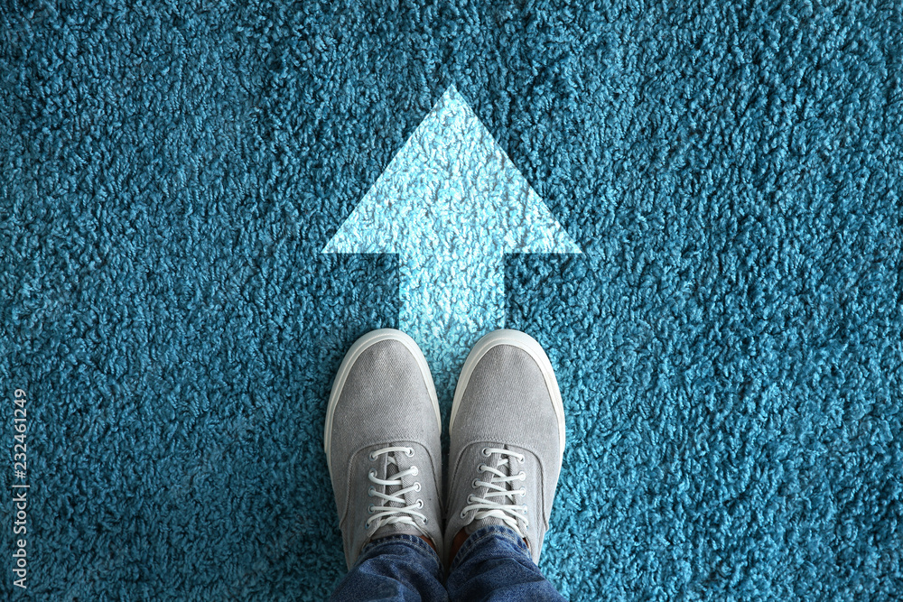 Fototapeta Man standing on carpet with arrow pointing in one direction. Concept of choice