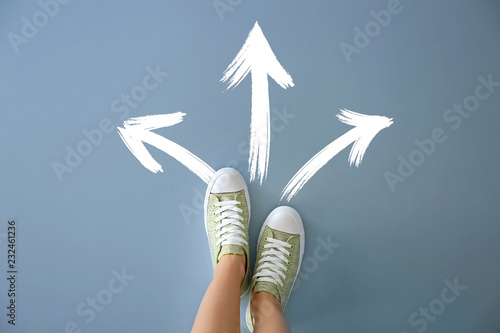 Photo Woman standing on color background with arrows pointing in different directions