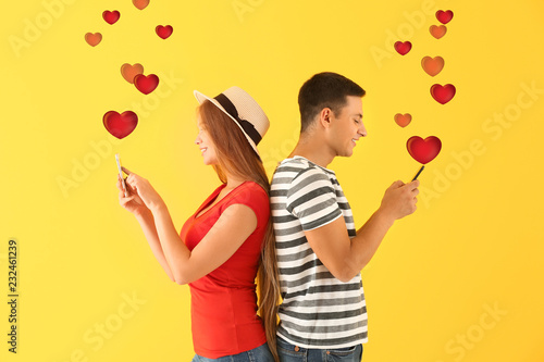 Fotografie, Obraz  Young couple with mobile phones on yellow background
