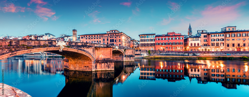 Fototapeta Picturesque medieval arched St Trinity bridge (Ponte Santa Trinita) over Arno river. Colorful spring sunset in Florence, Italy, Europe. Traveling concept background.