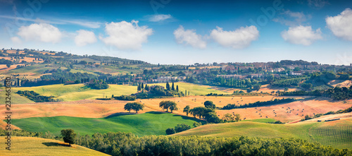 Papiers peints Bleu ciel Wheat harvest in Tuscany. Typical Tuscan view of San Quirico d'Orcia. Colorful summer view of Italian countryside. Beauty of countryside concept background.