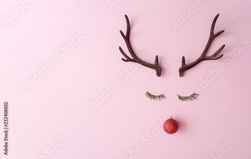 Fotomural Christmas reindeer concept made of evergreen fir, red bauble decoration and antlers on pastel pink background