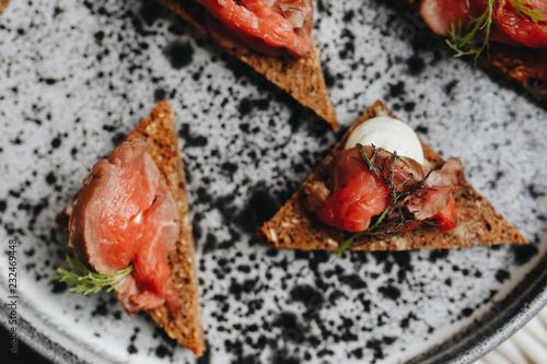 Fotografía  sandwiches with beef carpaccio on black bread.